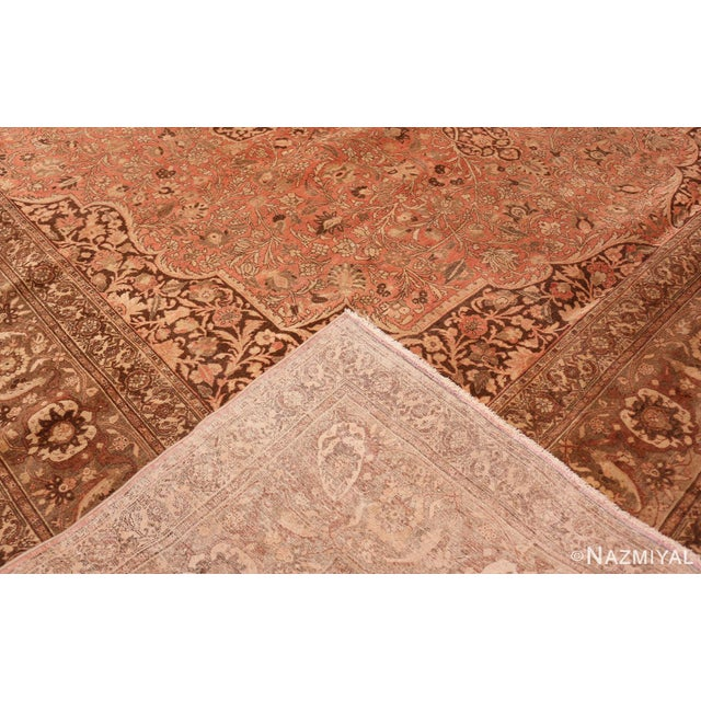 The warm hues of a rosy sunrise spread over this antique Persian rug, which features an ornate medallion at its center. A...