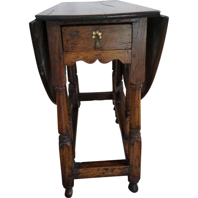 Details: Antique English oak drop leaf table circa 1780. This versatile table features a turned (block and tapering) gate...