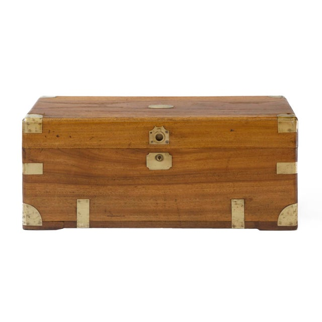 An antique Chinese small camphor wood chest on a later black painted stand. The original lock is without a key. The...