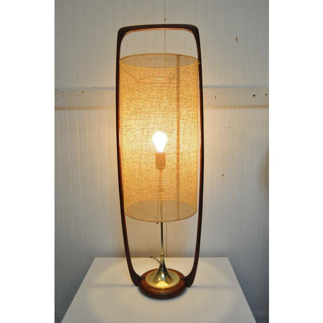 Very unique and large mid-century modern sculpted teak and brass table lamp with original woven shade by Modeline. Circa...