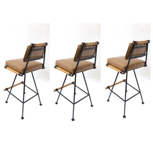 A set of three swivel barstools designed in the 1960s. Newly powered coated black lacquer and newly recovered in a soft...