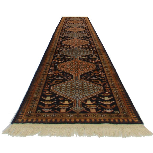Offered is a vintage Persian Ardebil runner rug. This hand knotted wool rug features a beautiful geometric design throughout.