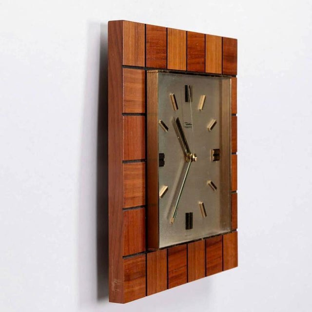 Mid-century square German battery-operated wall clock by Diehl is framed with squares of teakwood surrounding the white...