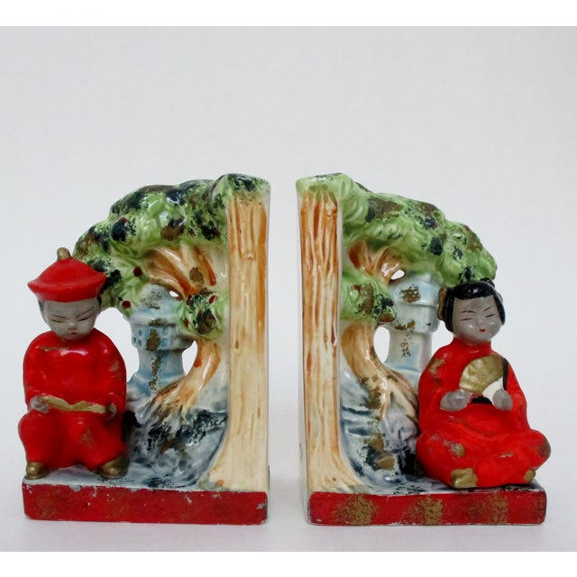 A pair of vintage Japanese hand-painted porcelain figurative bookends of a man and woman in traditional costume. Original...