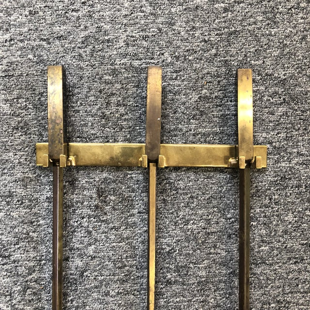 Beautiful set of hanging modern fire tools in solid aged brass. Includes broom, poker, shovel, and hanger. Brass screws...