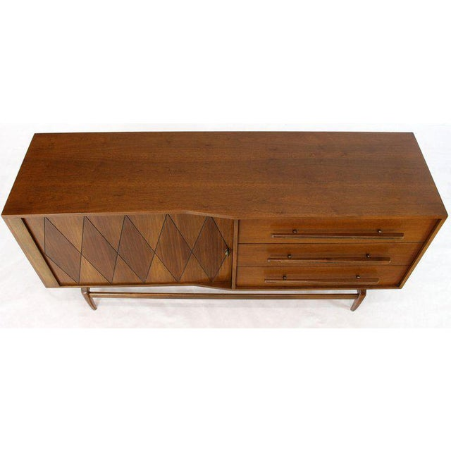 Mid-Century Modern tambour door walnut dresser with brass accents. Floating case over nice solid walnut sculptured base legs.