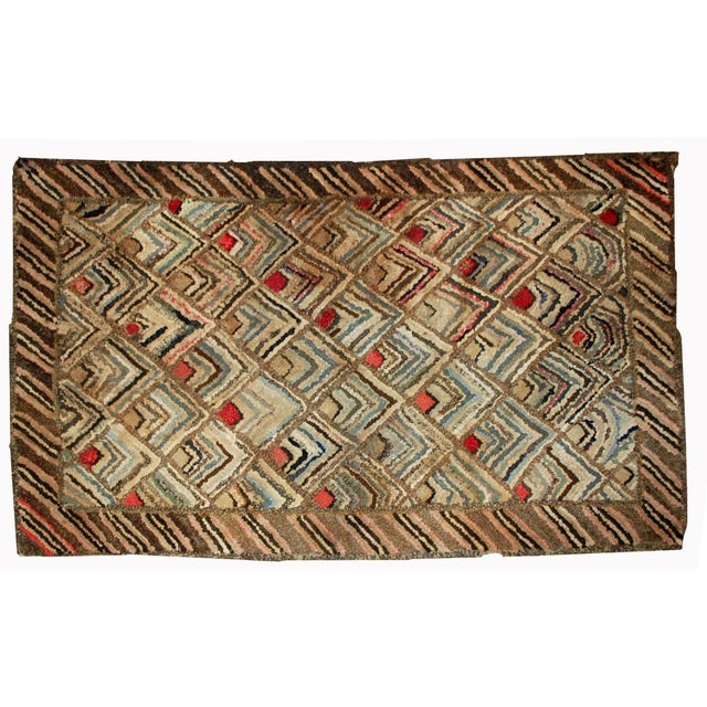 Handmade antique American geometric hooked rug in original good condition. The rug is made in repeating arrowhead shaped...
