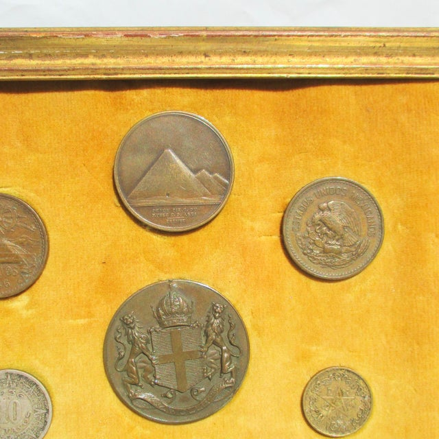 A framed collection of French Medallions, Mexican Pesos, Morrocan coins, Ancient Roman coin, and Catholic medallions....