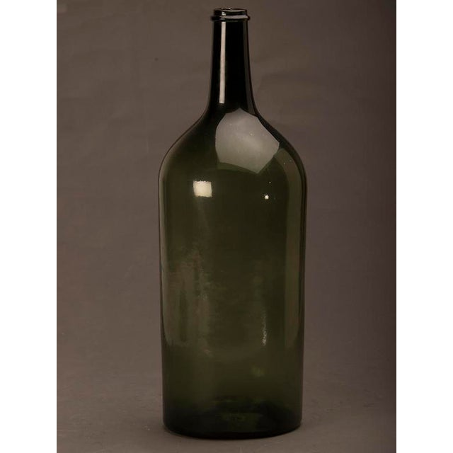 Tall green glass hand blown bottle from France c.1870. The tall and slender shape of this bottle gives it an interesting...