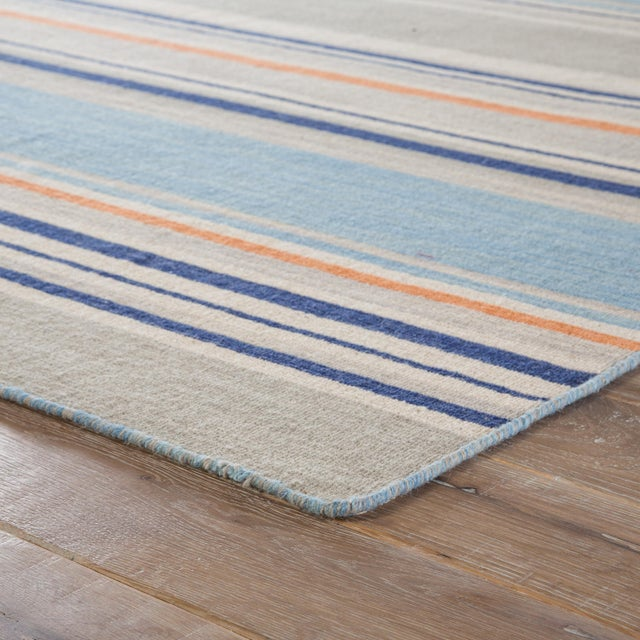 This classic dhurrie-style area rug features a contemporary coastal ticking stripe pattern in a blue, orange, and gray...
