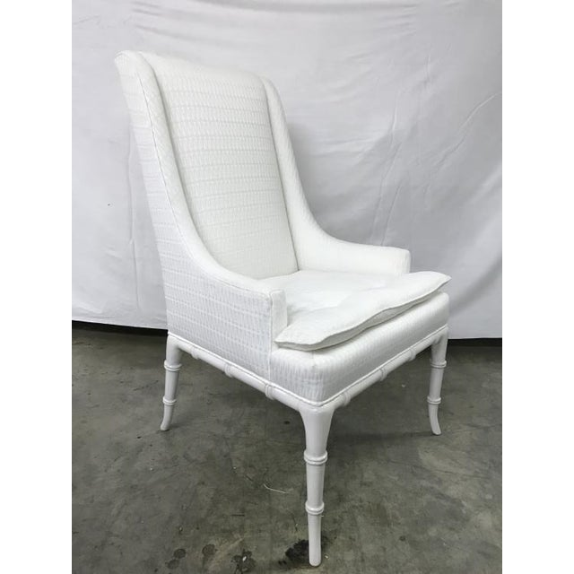 The Regan Host Chair is a first quality market sample that features a White Fabric with an Oyster Finish.