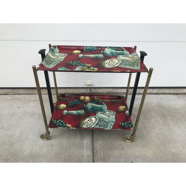 Gerlinol 1960's vintage folding 2 tier rolling bar cart with vivid Fornasetti style still life images on trays. Legs are...