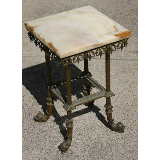 This small late 19th Century wrought iron side table with solid onyx slab top is brought to us from the collection of SF...