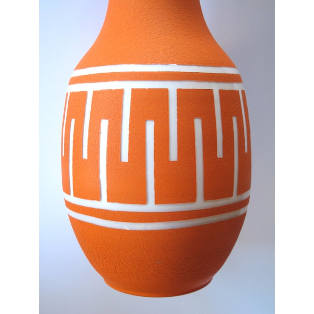 The tall vase of white cased-glass covered in an orange textured glaze adorned with a continuous fret band
