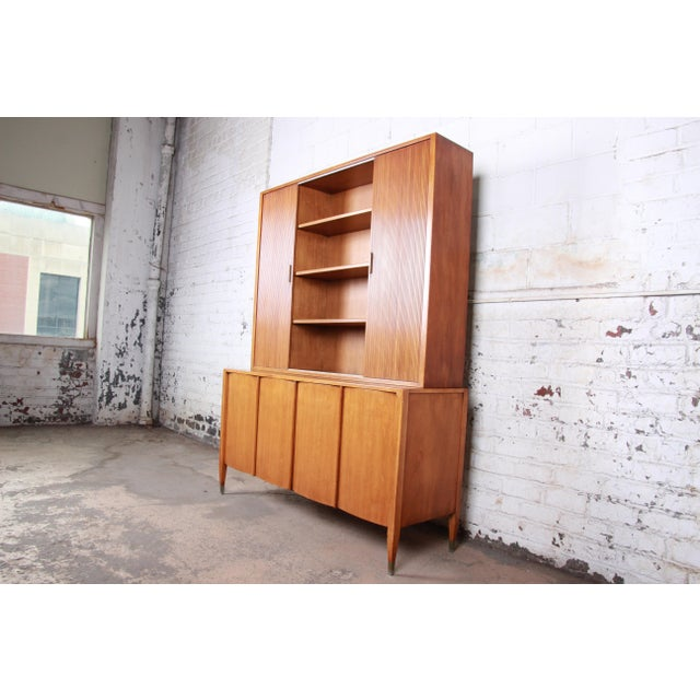 A gorgeous mid-century modern sideboard credenza with bookcase hutch top by Sligh Furniture of Grand Rapids. The credenza...