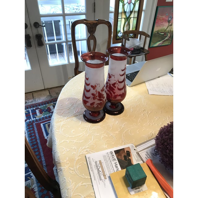 A pair of antique cranberry red hand blown glass vases. The two vases feature a cranberry red body with trees, birds, and...
