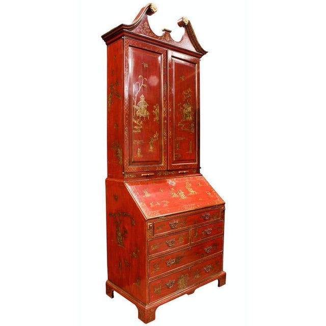 A George III style chinoiserie red lacquered bureau bookcase, the broken dentil cornice with gilt rosettes, over panel...