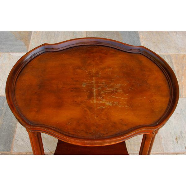 A vintage walnut veneer side table by Hekman Furniture. It features an oval top with convex curved sides and a moulded...