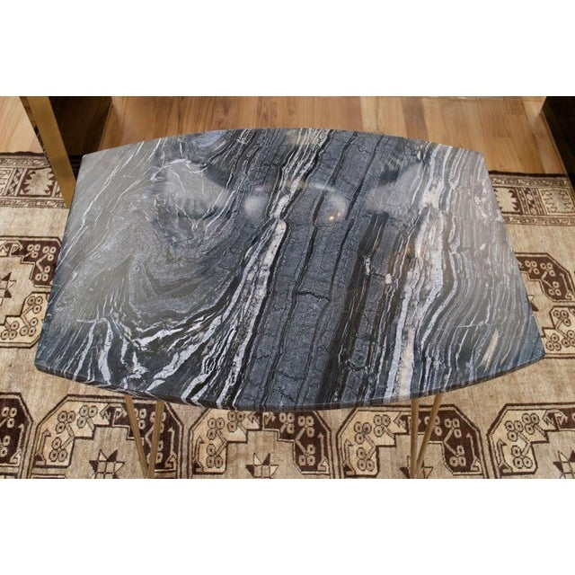 Brought to us from the design studio of Kendall Wilkinson. This beautiful variegated black marble tabletop sits upon a...