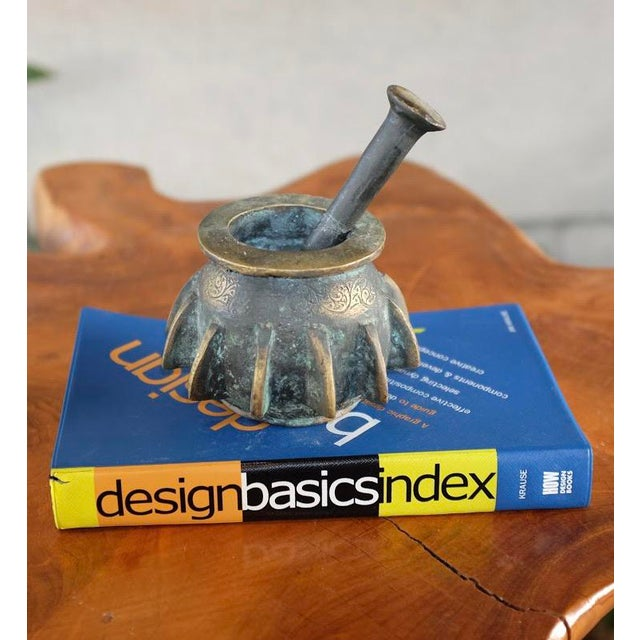 Patinated bronze mortar and pestle with carved patterns and blades fins extruded from the exterior. Amazing verdigris...