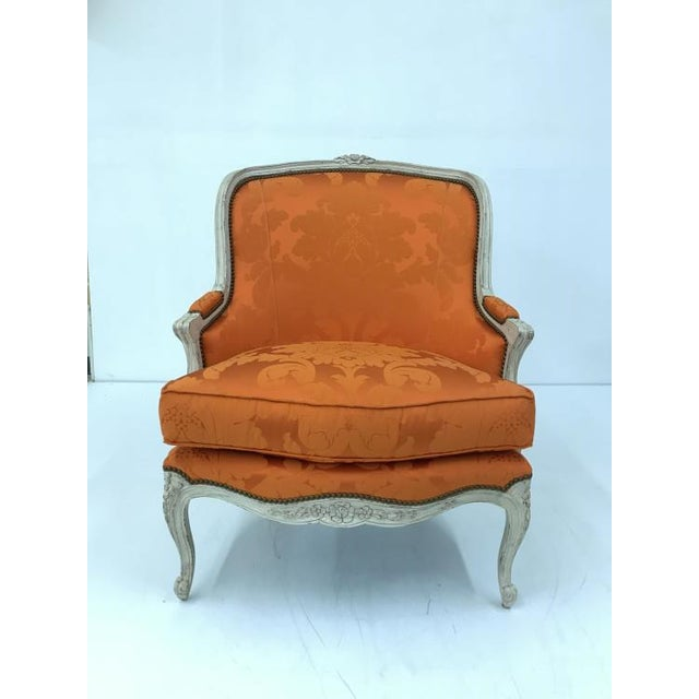 The Grande Duke Chair is a first quality market sample that features an orange patterned fabric with an ivory finish.