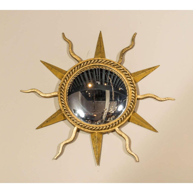 Attributed to Gilbert Poillerat, an exquisite hand-forged, gilt, wrought iron starburst, convex mirror with alternating...