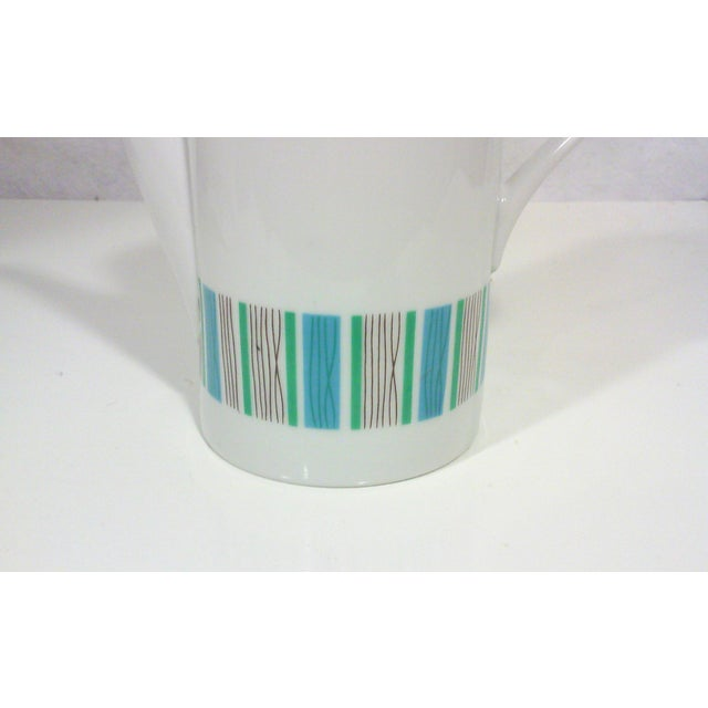 A Mid-Century Modern white porcelain coffee pot with a blue and turquoise stripe design around the perimeter of the base...
