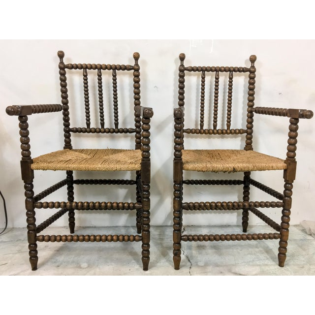 """Pair of antique French oak carved spool chairs with rush seats. Arm; 29"""". Seat; 20""""."""
