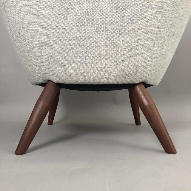 Oda, designed in 1953 by Nanna Ditzel in Ditzel's Hallingdahl fabric. Teak legs and teak arm rests.