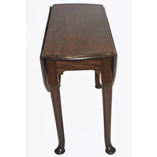 an English, period George III / circa 1760, drop leaf dining table, round, with shaped cabriole legs and pad feet, hinged...