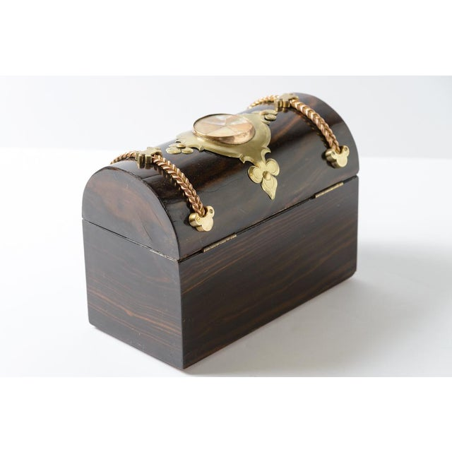 Coromandel wood box with elaborate brass and mother of pearl cartouche on top. The interior is lined with pink crushed...