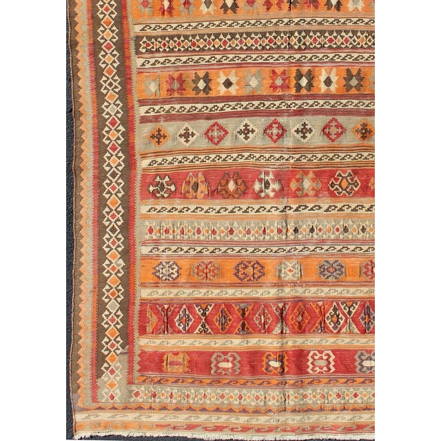This colorful antique kilim displays faded orange-red, yellow, red, brown and gray stripes. The embroideries and details...