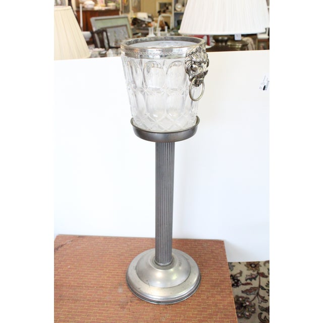 """Glass and silver plated ice bucket with lion's head handles and silver aluminum pedestal table. Ice bucket: 10x7.5x8.5""""...."""