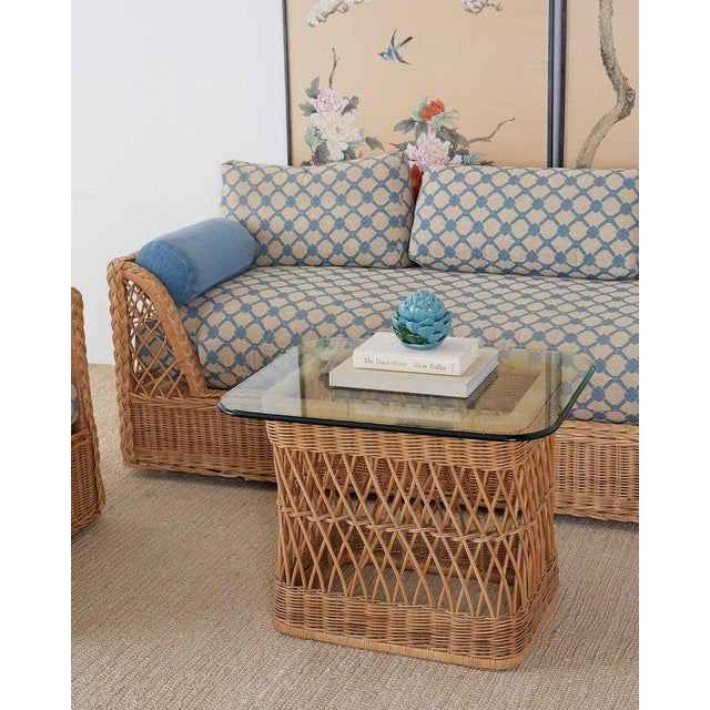Organic modern style coffee cocktail table made by McGuire featuring a woven rattan wicker frame topped with a thick pane...