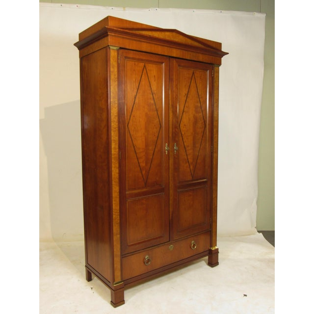 An Empire style inlaid black cherry armoire/wardrobe by Baker Furniture Company with inlaid ebony detail, burlwood accents...