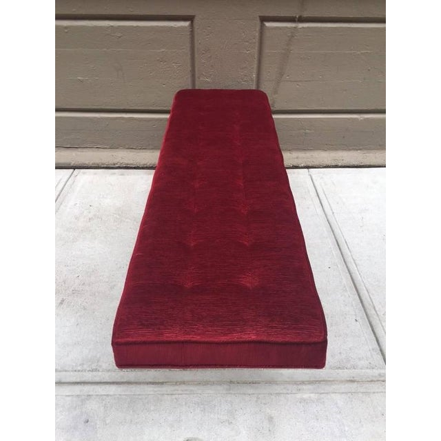 Tufted bench with a brushed steel base in the style of tufted bench style of Poul Kjærholm. Upholstery is of a plum red...