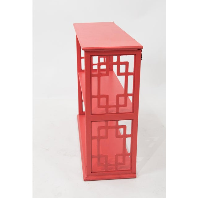 Stylish mid-century chinoiserie style etagere in wood. Painted in chinese red. Designed to be wall hung; however would...