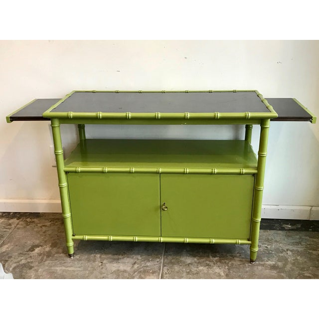 Avocado Green lacquer with faux bamboo trim, this cabinet perfect as a bar cabinet. 2 side leaves extends another 12...