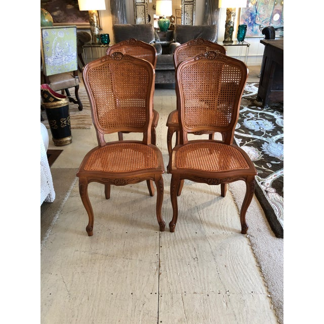 A Classic French style set of 4 side dining chairs having carved wood frames and caned backs and seats. Measures: Seat...