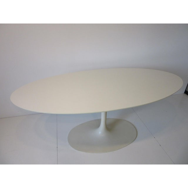 A slender tulip based desk / dining table with white laminate top and metal base in a rare size that can work as a desk or...