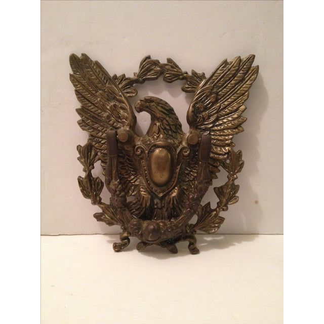 Detailed eagle door knocker with a front crest. Worn brass plating; in original condition. This could be a bronze, it is a...