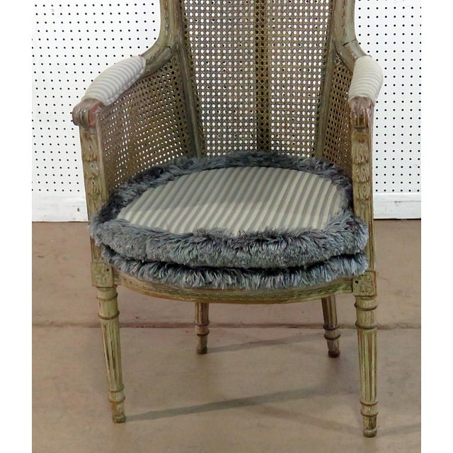 Louis XV style distressed painted armchair with caned seat, sides, and back. Includes removable cushion.