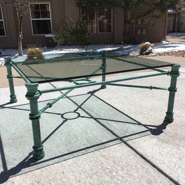 Large square faux bronze wrought-iron base with patinated bronze verdigris finish, and heavy rounded edge glass in-set...