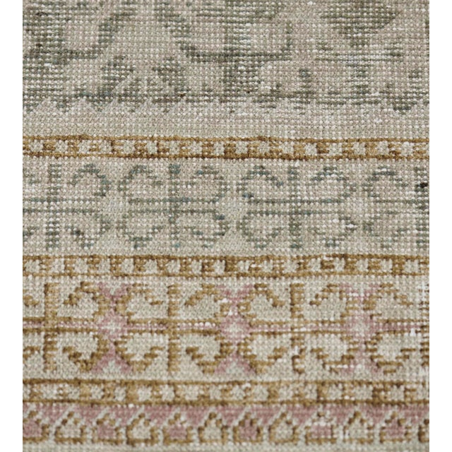 This antique Khotan rug has a mole-grey field with an overall design of ivory pomegranate vines issuing angular floral...