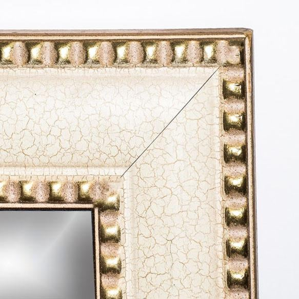 Contemporary wall mirror that is framed in an off white cream toned crackle finish that is flanked to the outer and the...