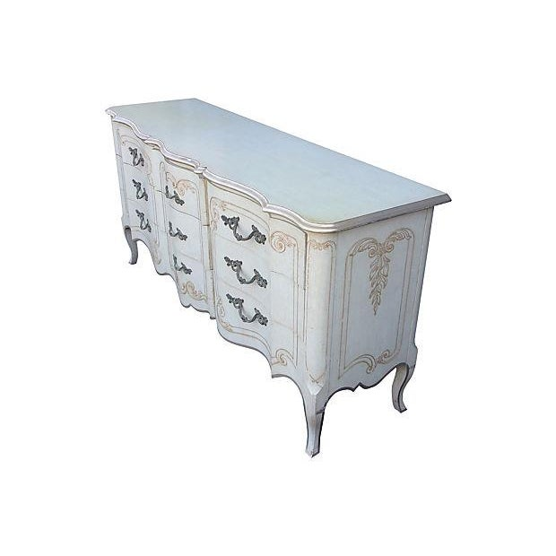 A John Widdicomb French style Nine Drawer Dresser. Scalloped top surround in a beautiful burnished silver leaf, burnished...