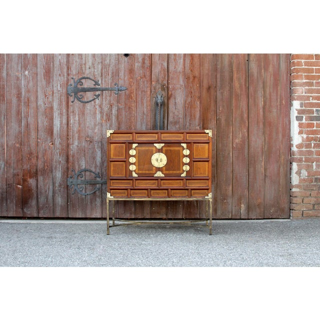 A paneled Korean chest with cross-handed front. It features double doors that open for ample storage, containing brass...