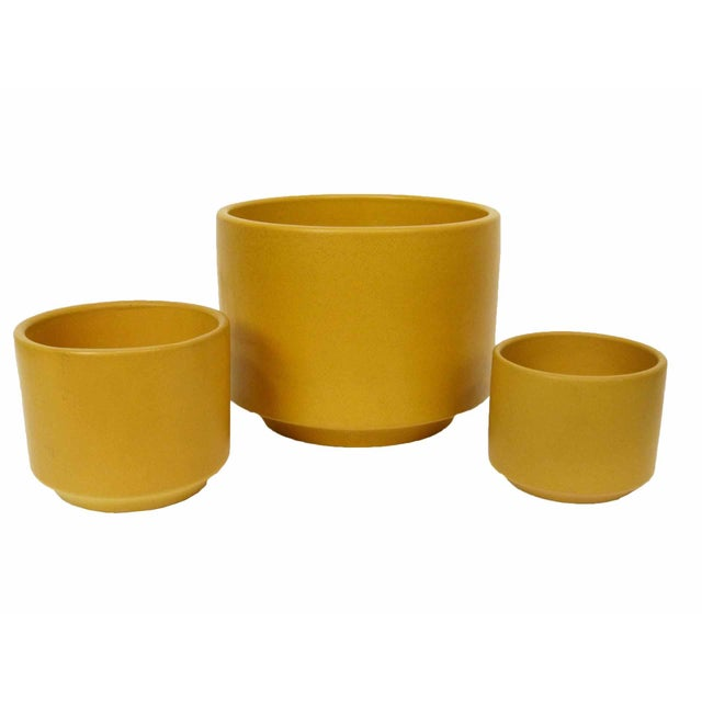 A set of 3 mid century modern mustard yellow planters by Gainey Ceramics of Laverne, CA. The set includes one C-6, one C-8...
