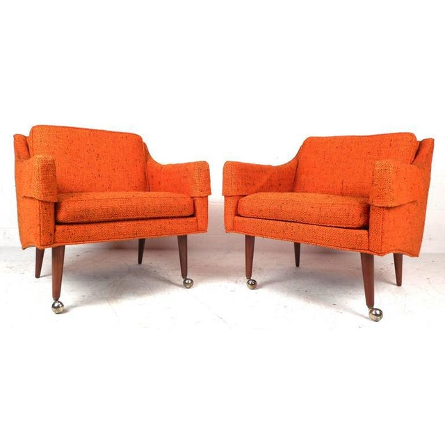 """This stunning set of four rare mid-century armchairs features magnificent vintage upholstery, 16"""" seat height, and tapered..."""