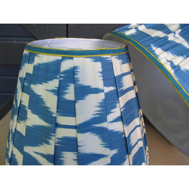 """A pair of hand made pleated ikat lampshades, embellished with vintage trim. Measurements Top 9"""" Side 13.5"""" Bottom 17"""""""